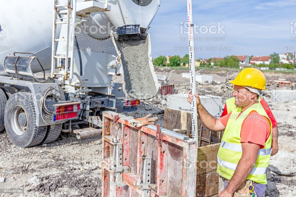 Holding leveling rod to measuring level on construction site stock photo