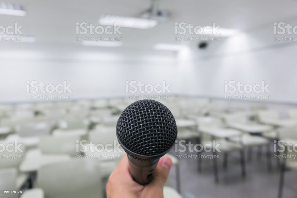 Holding microphone in hand in classroom stock photo