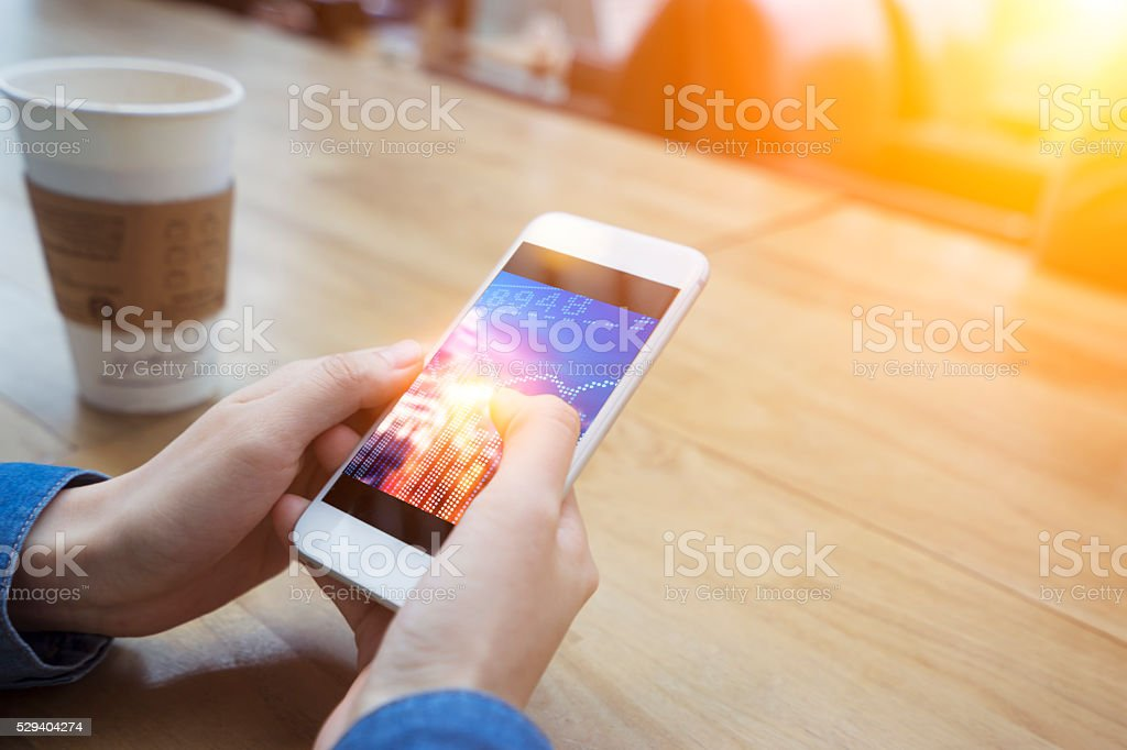 holding mobile phone in a cafe stock photo