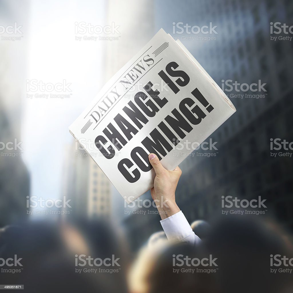 Holding Newspaper with Change Comes stock photo