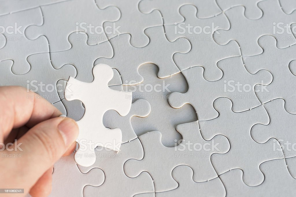 holding one blank white piece of jigsaw puzzle stock photo