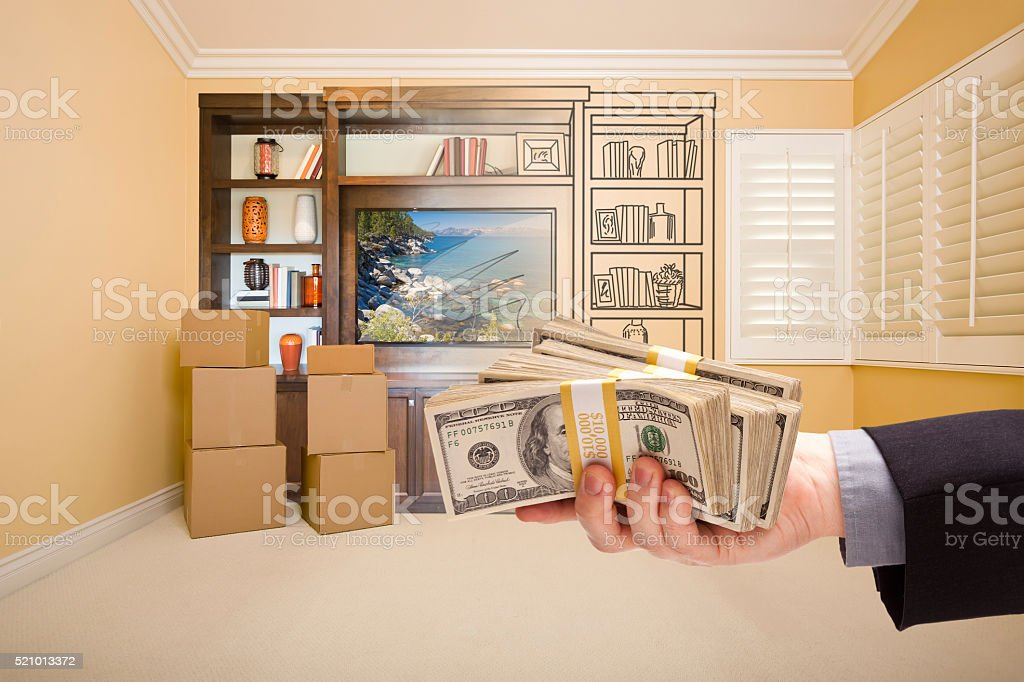 Holding Out Cash Over Drawing of Entertainment Unit In Room stock photo