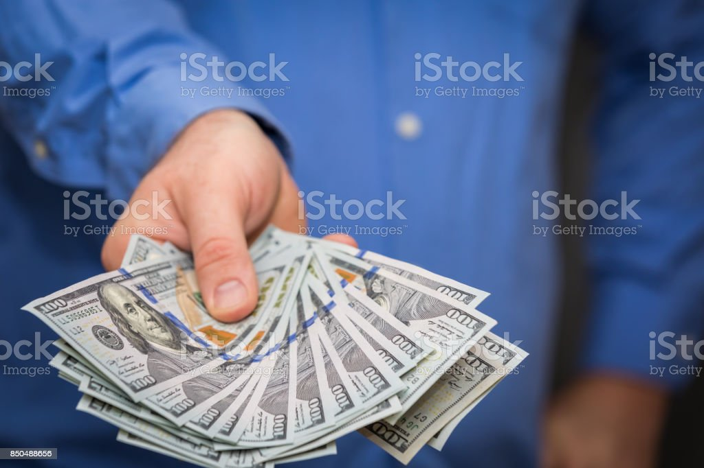 Holding Out Fanned Hundreds stock photo