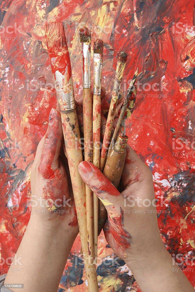 Holding paintbrushes royalty-free stock photo