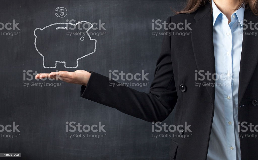 Holding piggy bank drawing front of blackboard stock photo