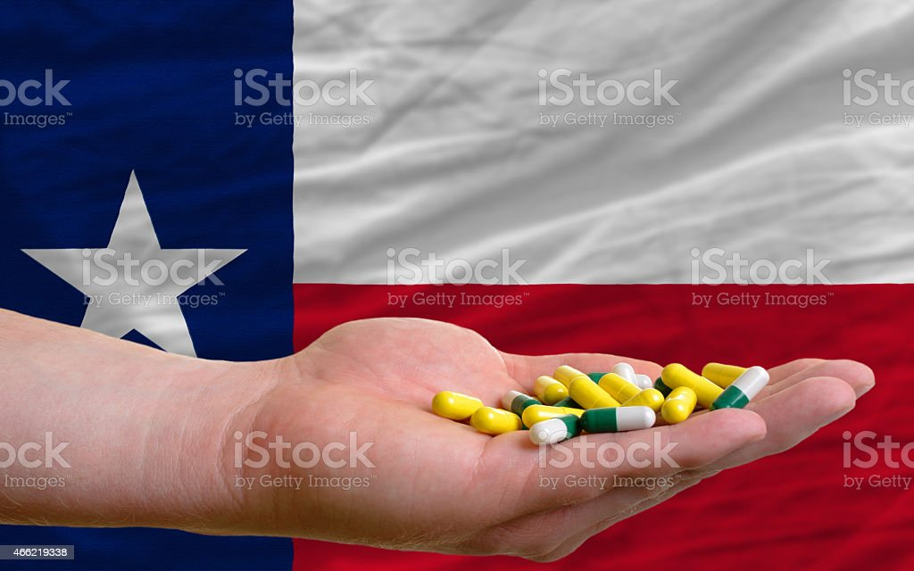 holding pills in hand and flag of texas stock photo