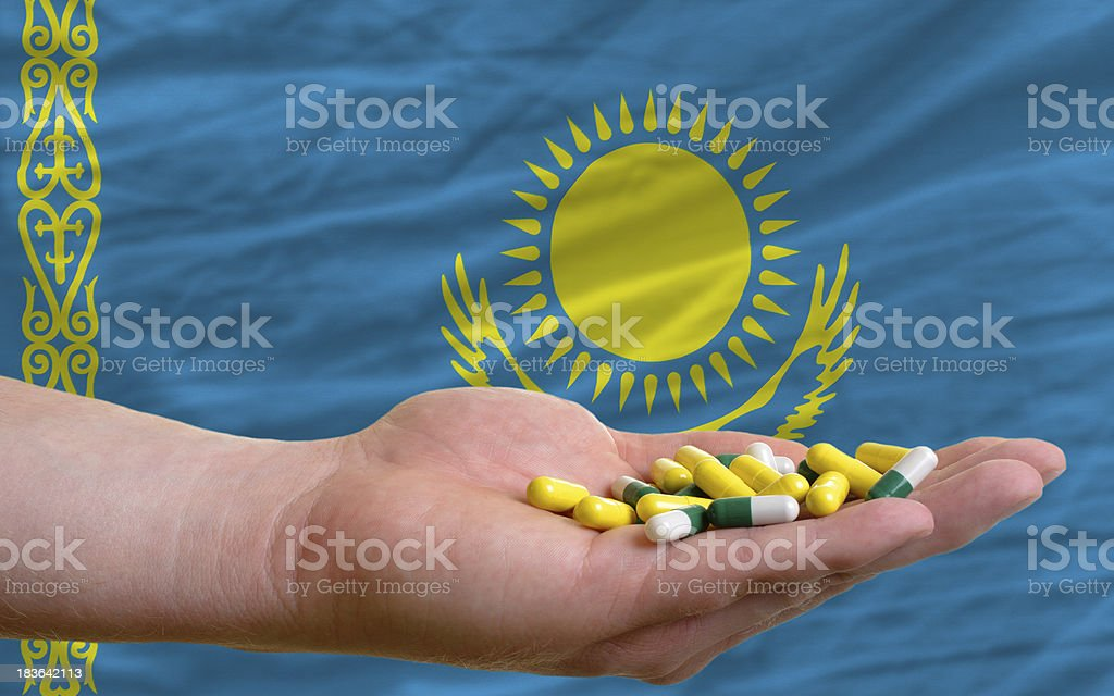 holding pills in hand front of kazakhstan national flag stock photo