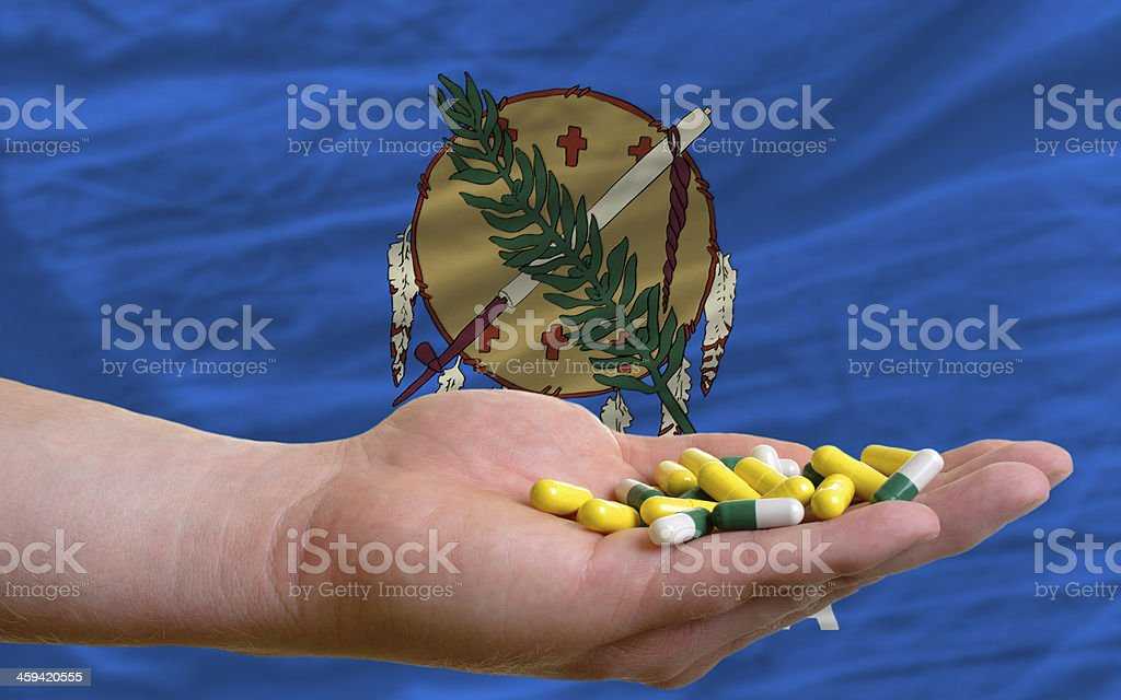 holding pills in hand front of oklahoma us state flag royalty-free stock photo