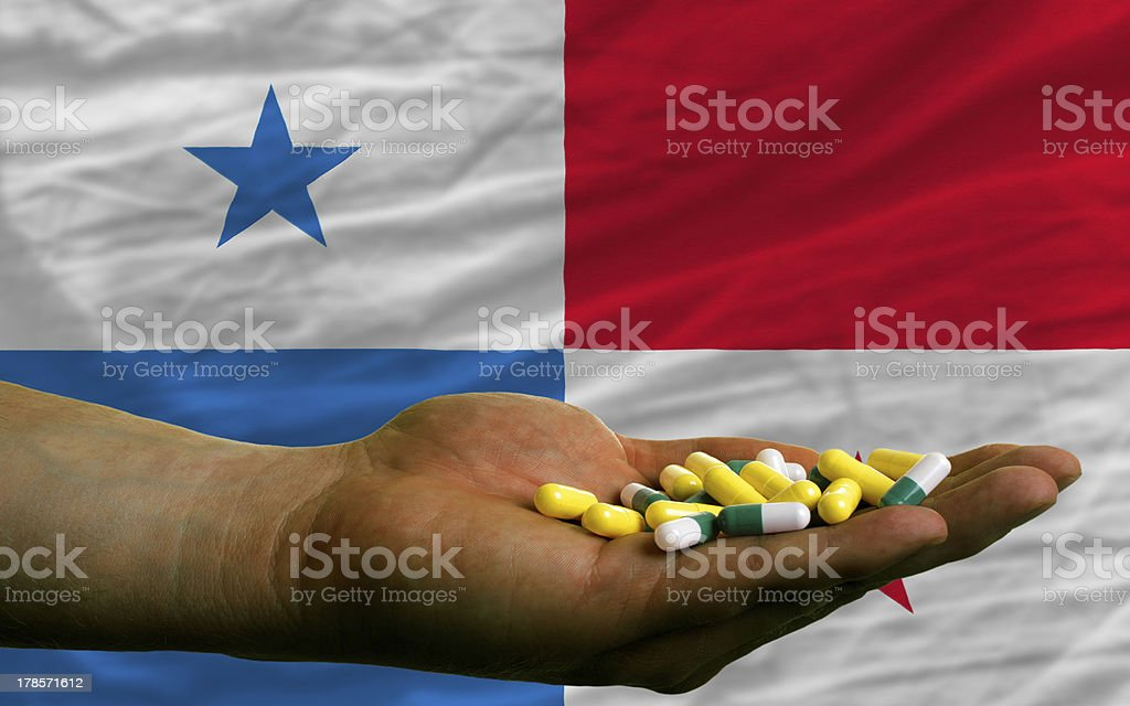 holding pills in hand front of panama national flag royalty-free stock photo
