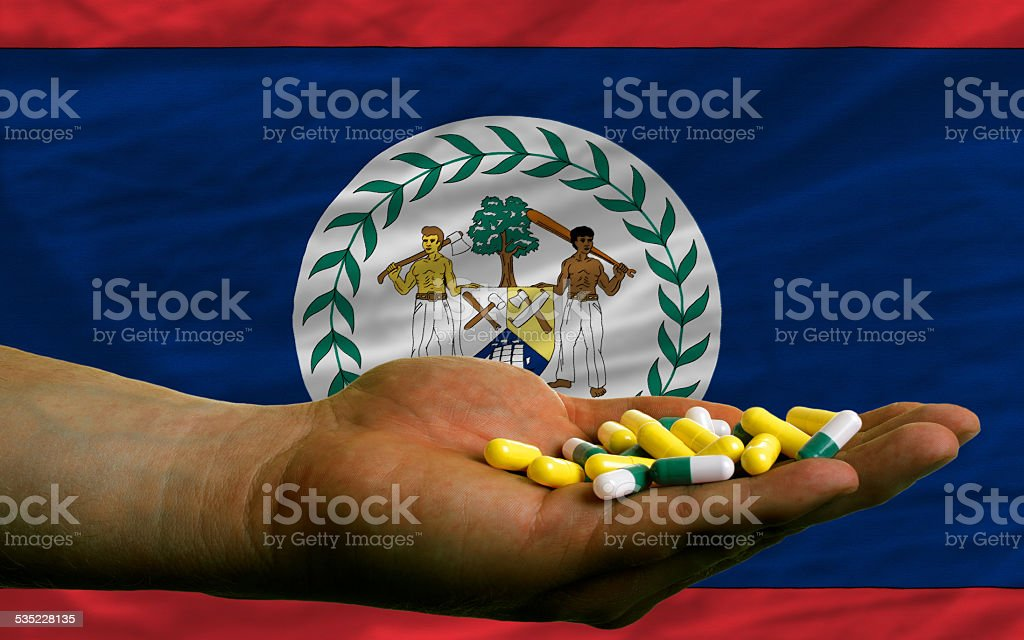 holding pills in hand in front of belize national flag stock photo