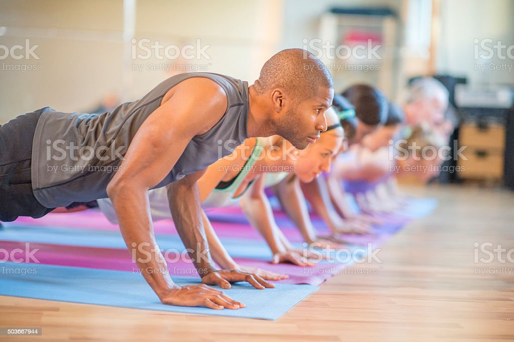 Holding Plank Pose in Yoga Class stock photo