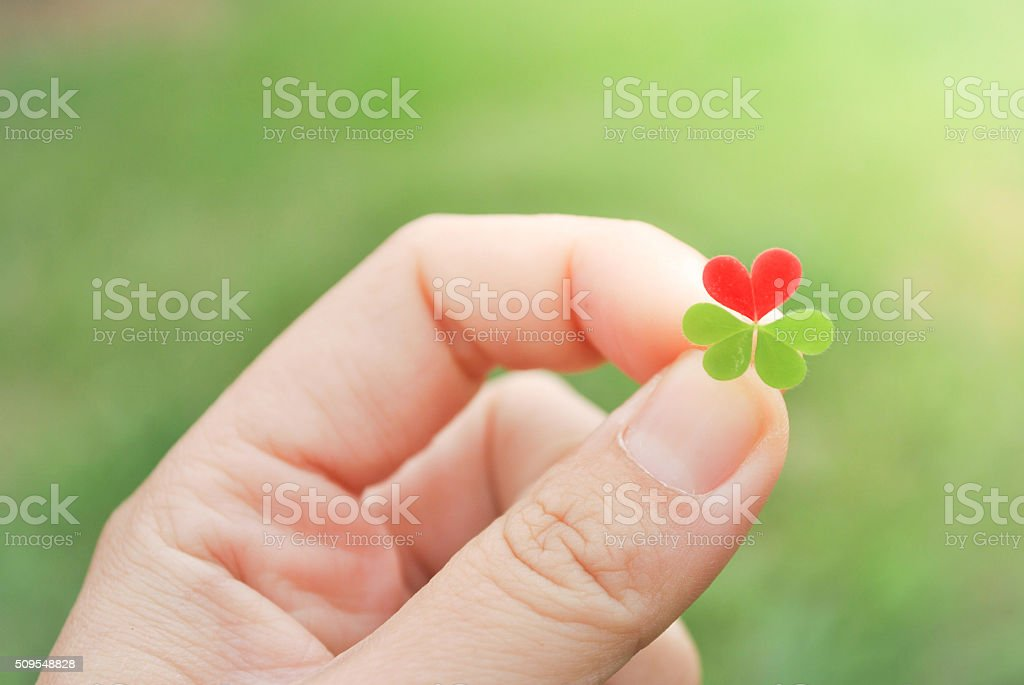 Holding red hear clover leaf for Valentine's day stock photo