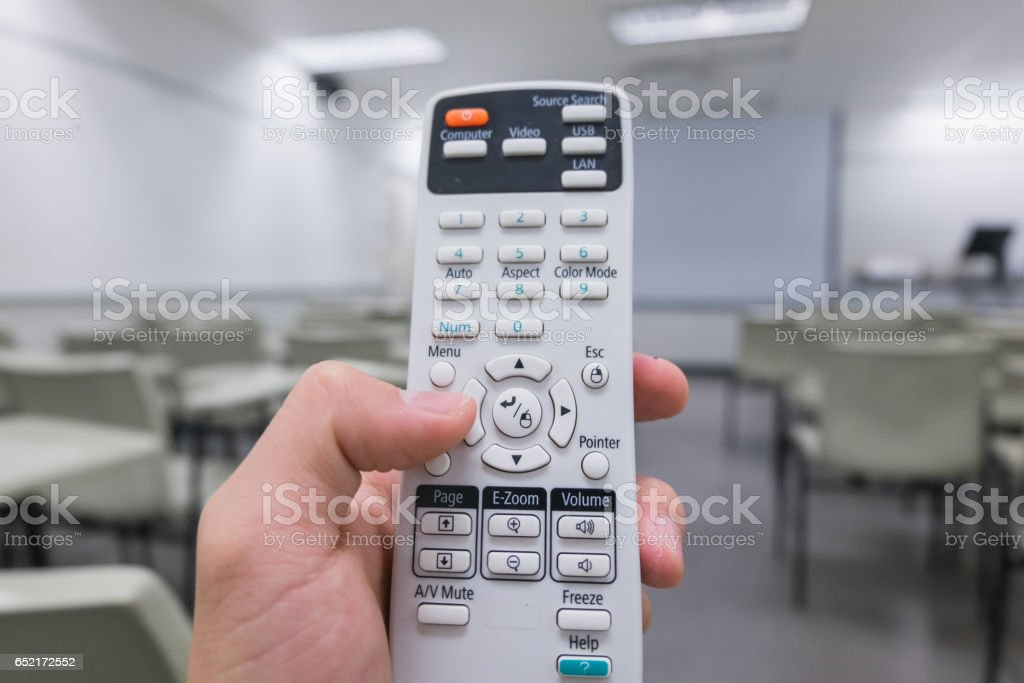 Holding remote control  projector in hand in classroom stock photo