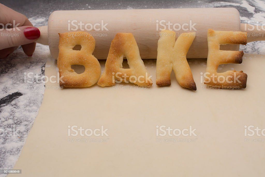 holding rolling pin with word bake  on black counter stock photo