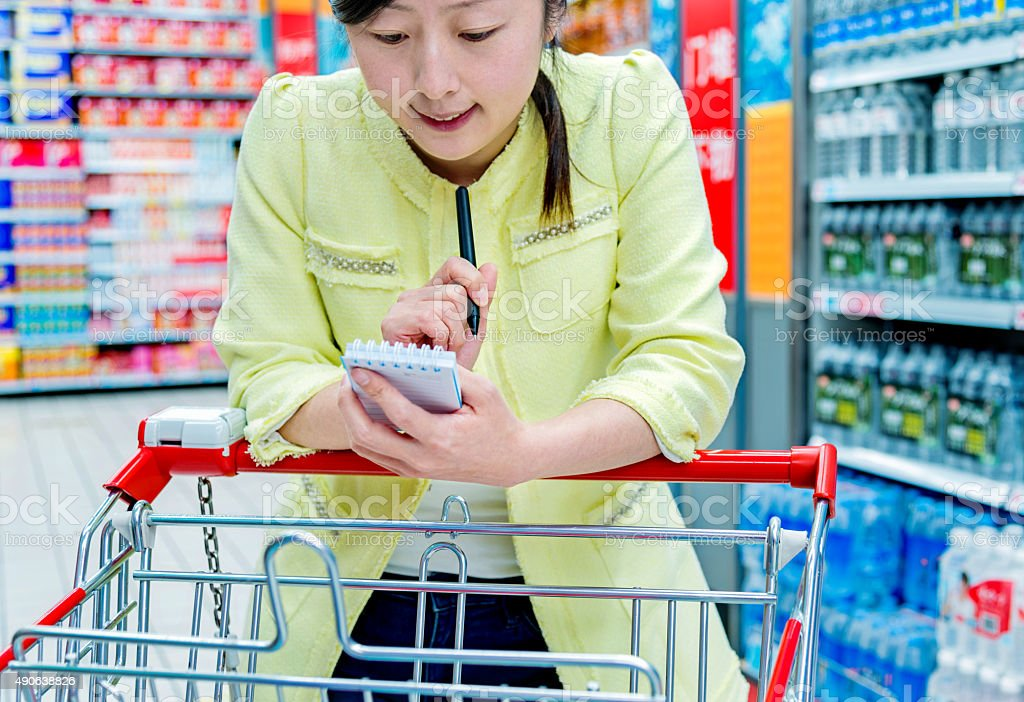 Asian attractive woman holding shopping list in a supermarket.