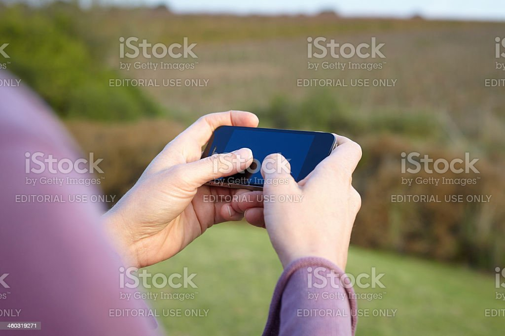 Holding smartphone horizontal and typing with thumbs royalty-free stock photo