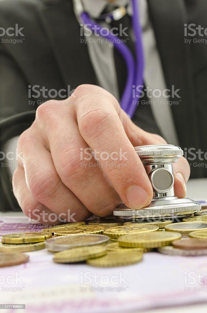 Holding stethoscope on Euro money stock photo