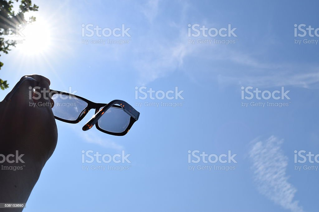 holding sunglasses at the sun summer background stock photo