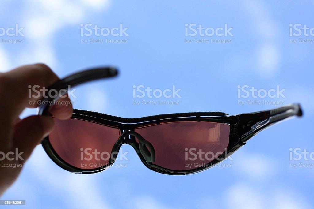 Holding sunglasses toward sky stock photo