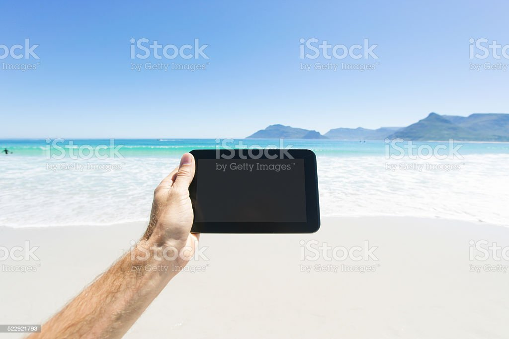 Holding tablet PC in tropical paradise stock photo