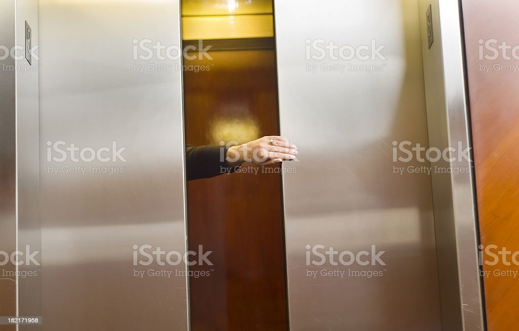 Holding the elevator door stock photo