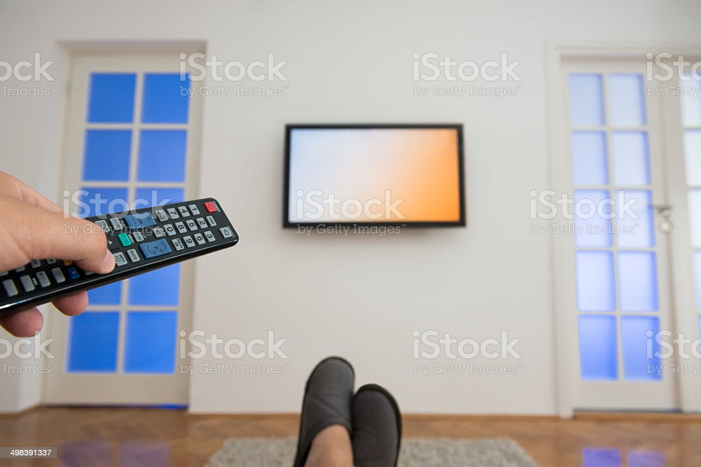 Holding TV remote control with a television as background stock photo