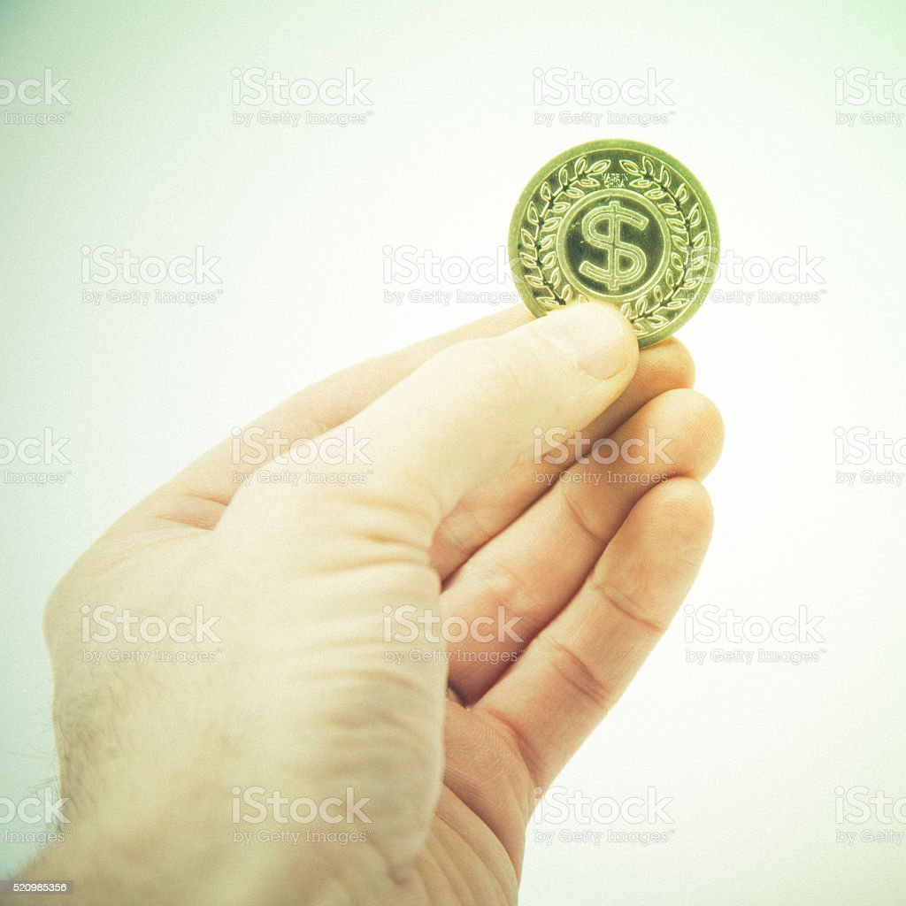 Holding up gold metal dollar sign coin stock photo
