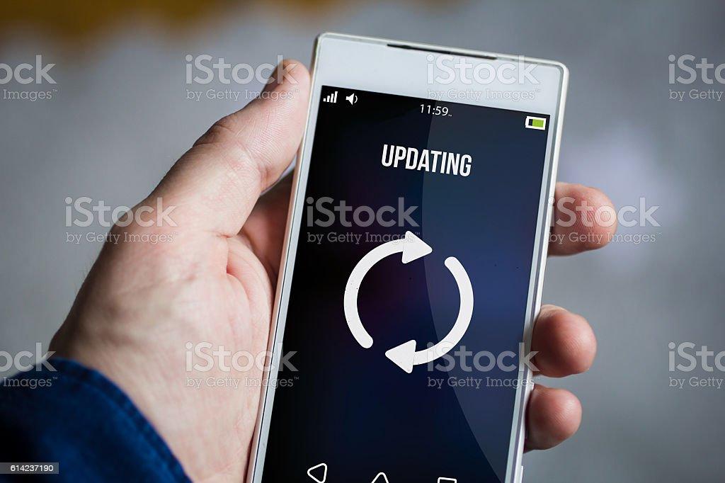 holding updating smartphone stock photo
