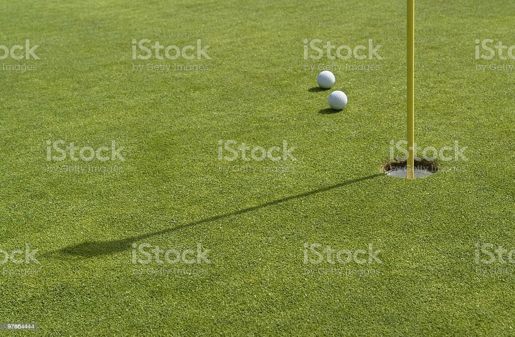 hole and golf balls in green back royalty-free stock photo