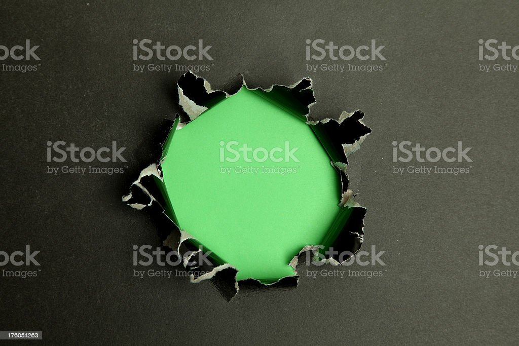 Hole in black paper with a green background behind it royalty-free stock photo