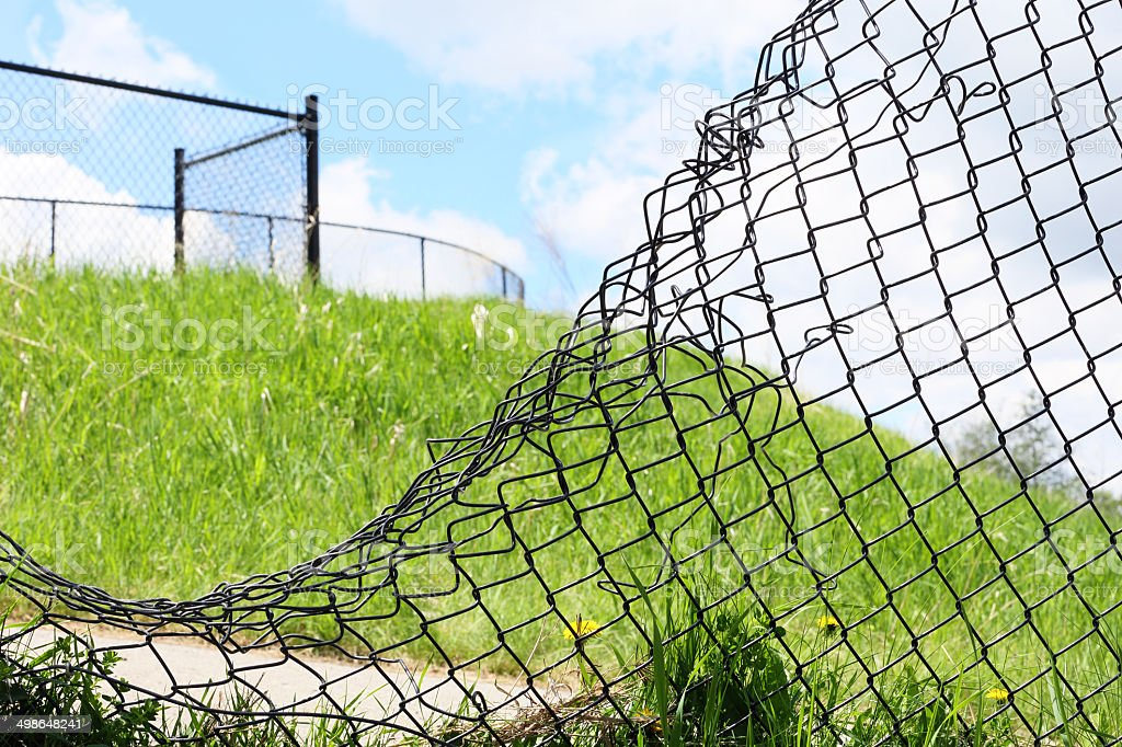 hole in fence stock photo
