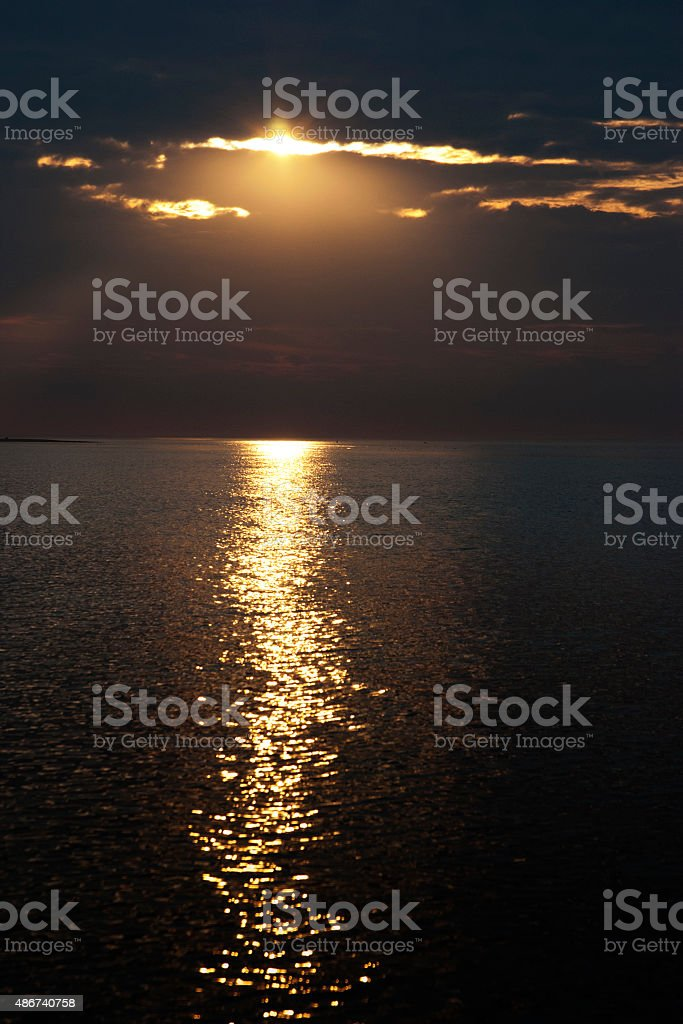 Hole in overcast sky with sunbeams over water horizon stock photo