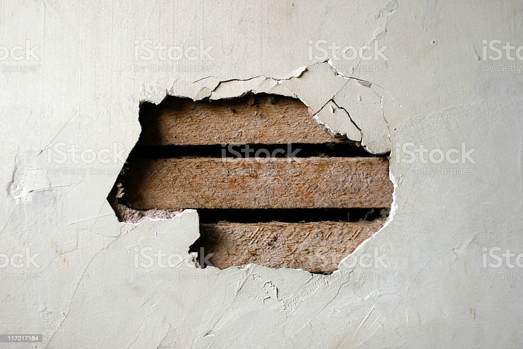Hole in Plaster Wall - Exposed Wood Paneling stock photo