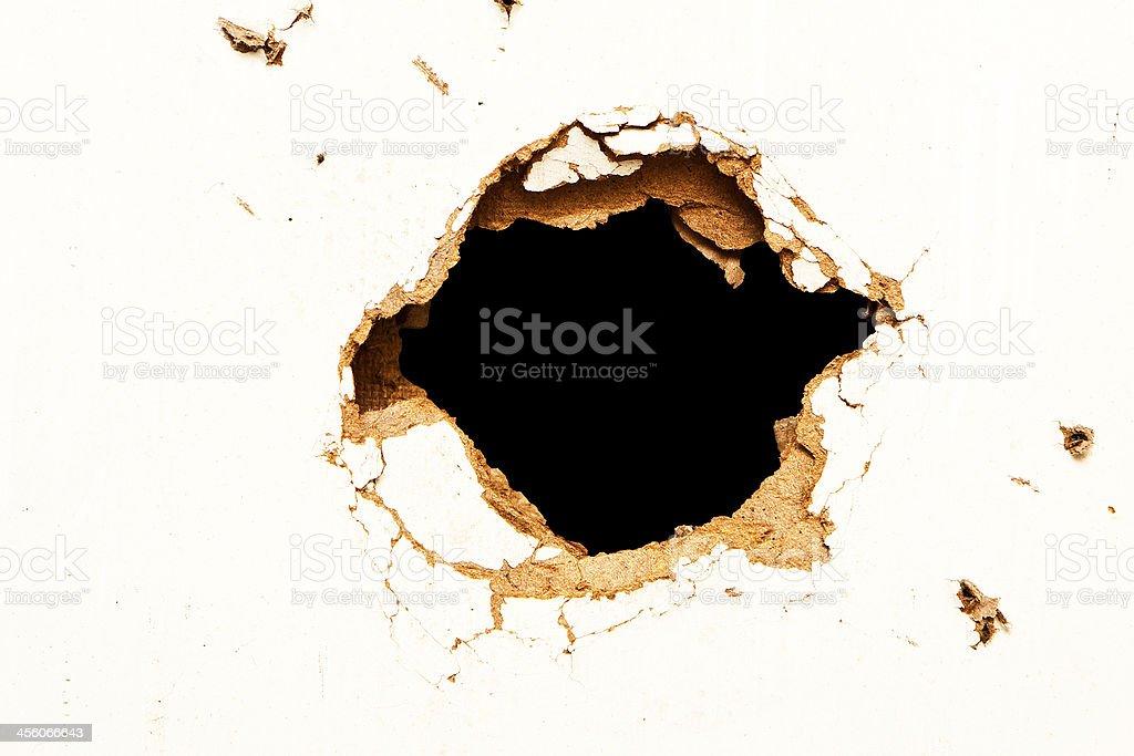 Hole in the fibreboard stock photo