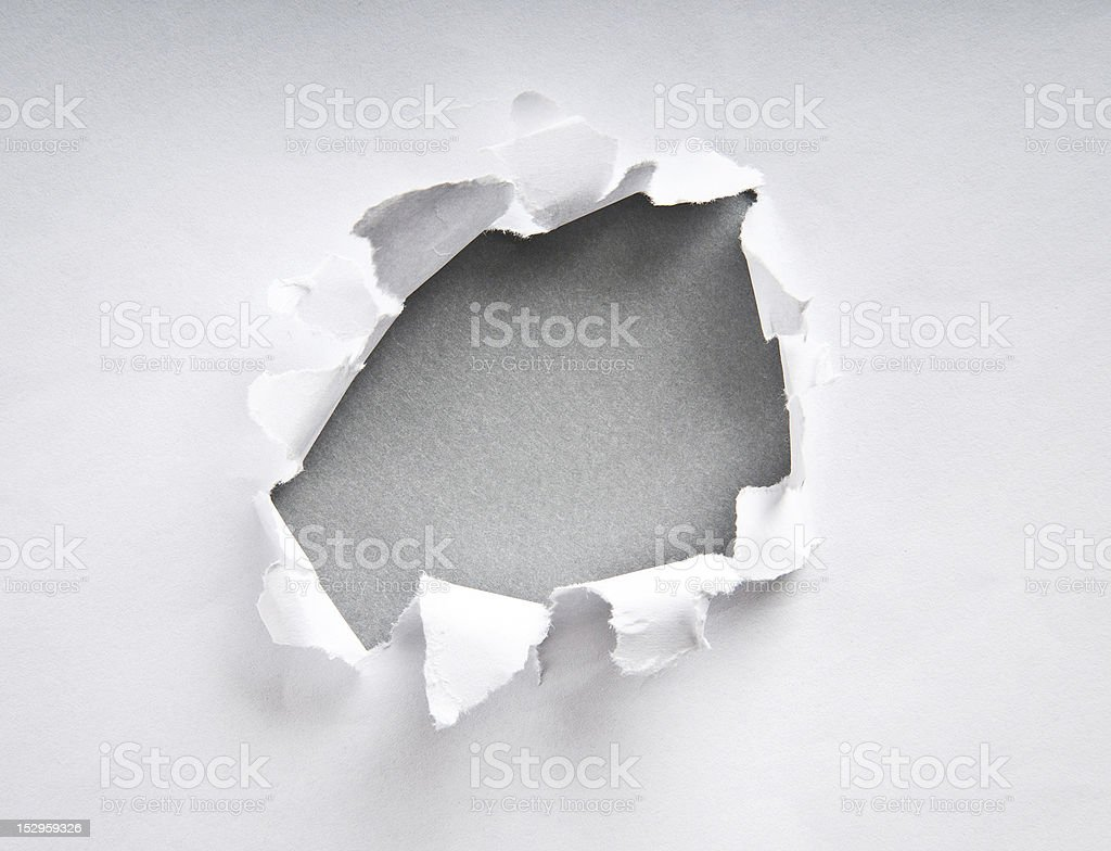 Hole in the paper with torn sides stock photo