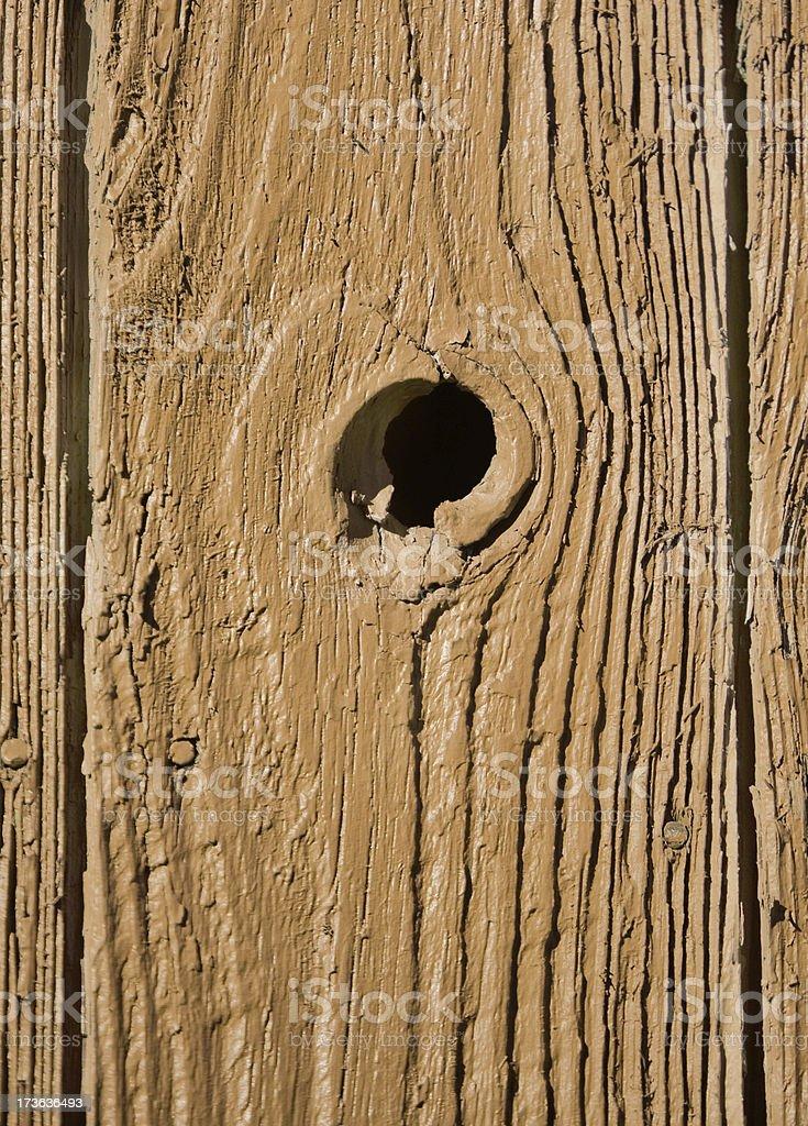 a wood plank with a knot hole;