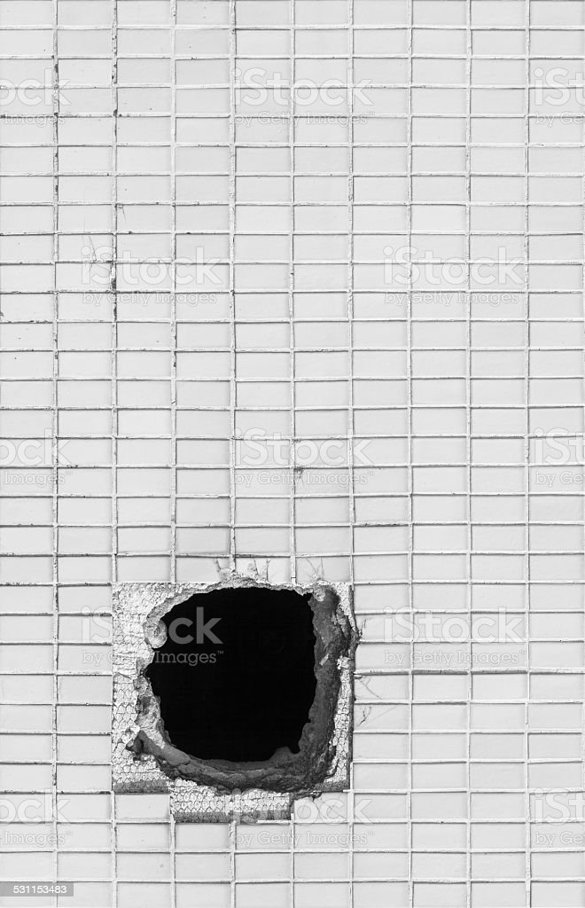 Hole on the old white wall stock photo
