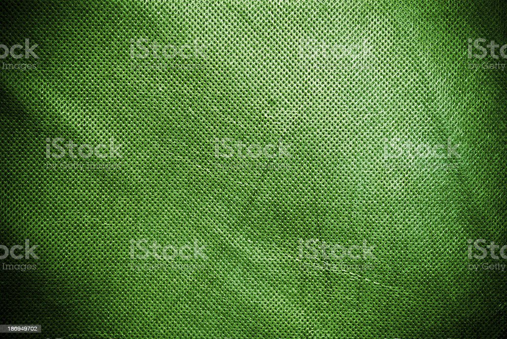 Holed and creased green canvas background or texture royalty-free stock photo