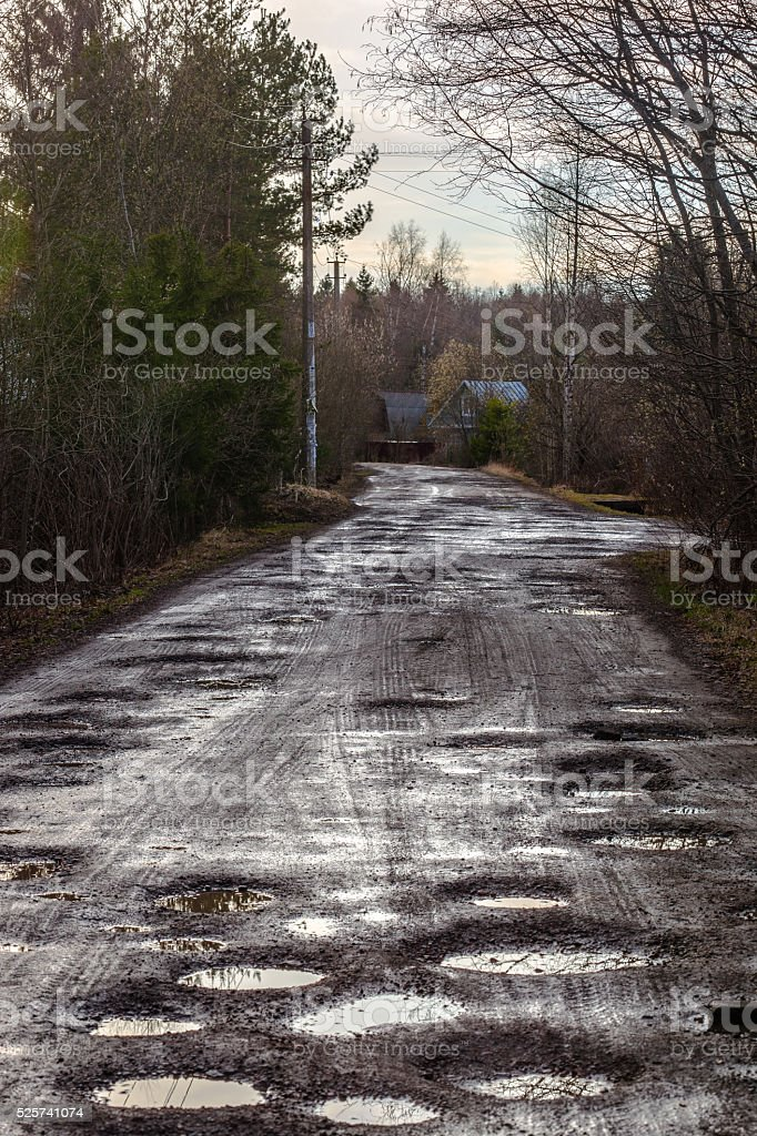 Holes and pothole on  rural road after rain in spring stock photo