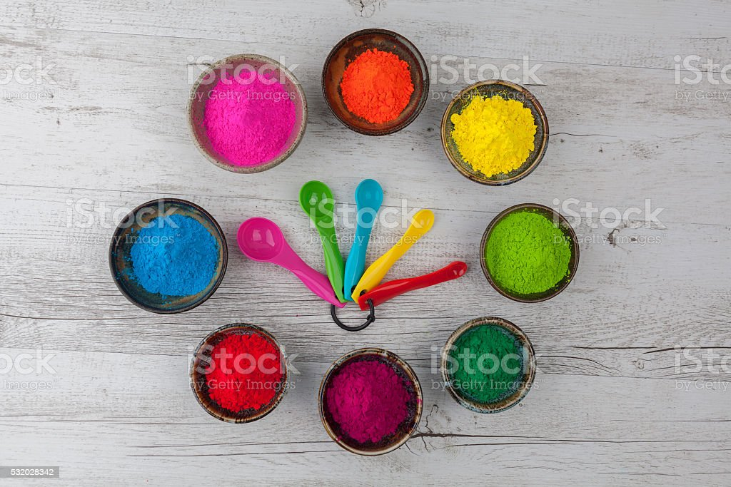 Holi powder in cups arranged in circle with measuring spoons stock photo