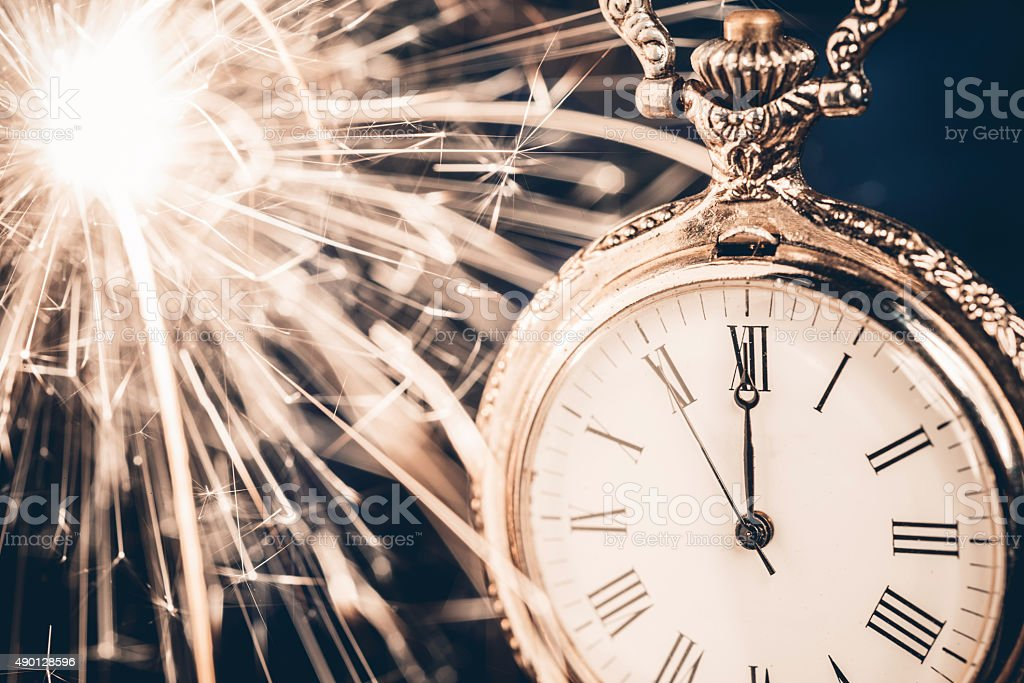 Holiday background with a sparkler and new year clock stock photo