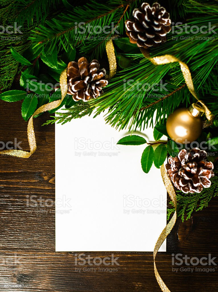 Holiday background with real greenery, pinecones and blank invitation stock photo
