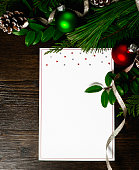 Holiday background with real greenery, pinecones and blank invitation