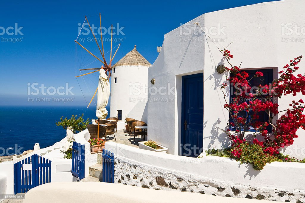 holiday bungalow and windmill in Oia Santorini royalty-free stock photo