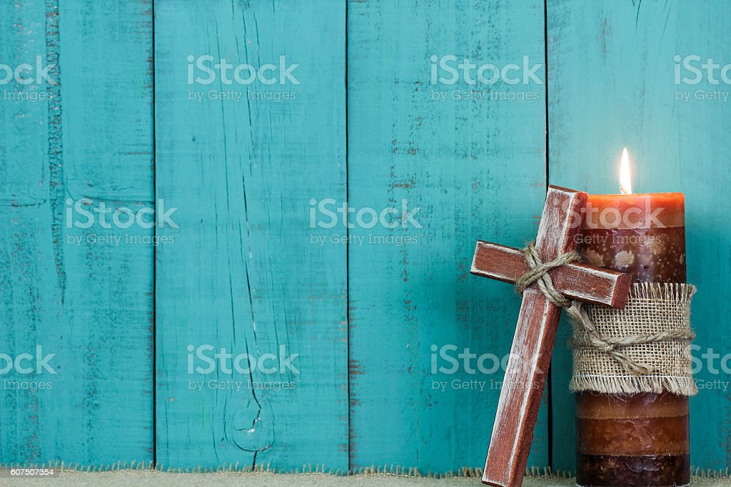 Holiday candle and wood cross stock photo