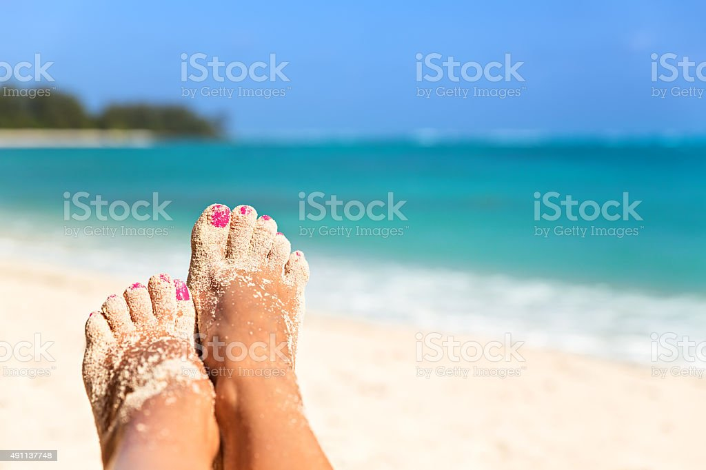 Holiday concept. Woman feet close-up relaxing on beach, enjoying stock photo