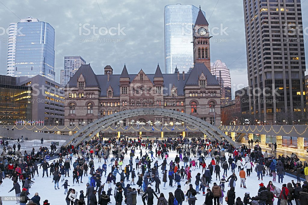 Holiday crowd ice-skating in Toronto square at dusk stock photo