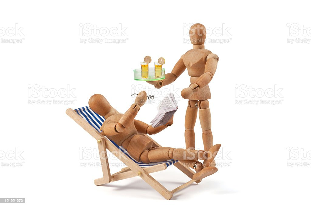 Holiday dream - wooden mannequin in deckchair with drink royalty-free stock photo