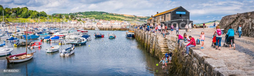 Holiday families catching crabs on The Cobb Lyme Regis Dorset stock photo