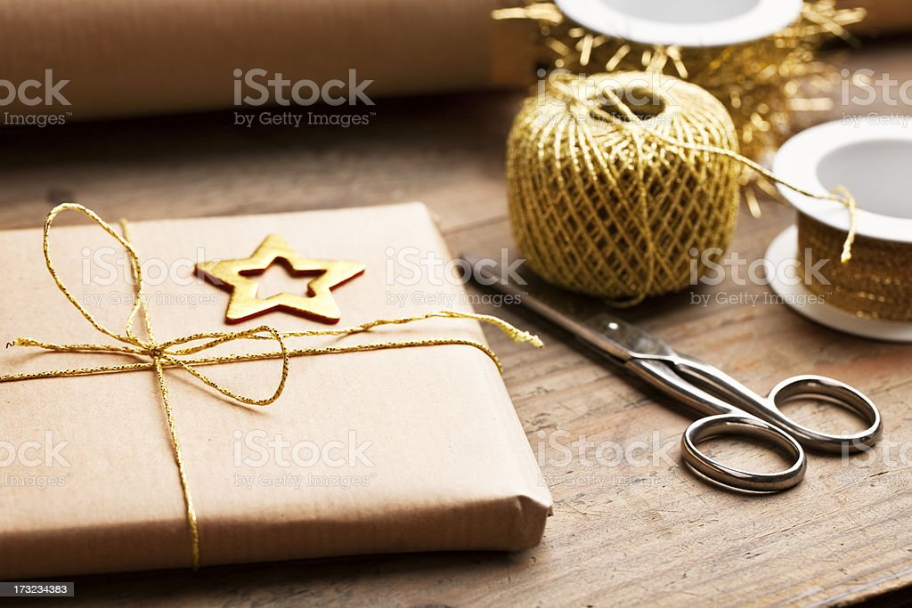 Holiday gift wrapped in eco-paper with gold ribbon stock photo